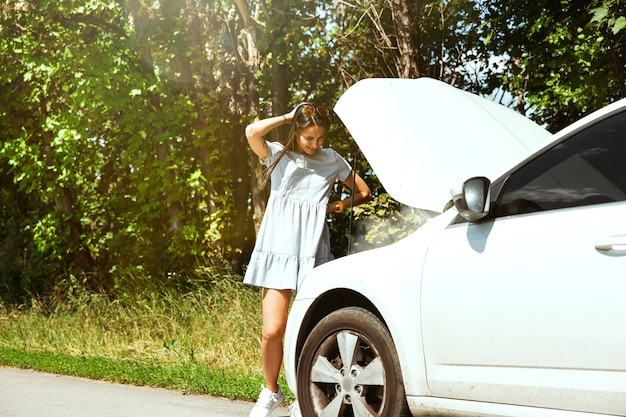 若い女性は休憩の途中で車を壊した。彼女は自分で壊れたものを直そうとしている、またはヒッチハイクする必要があります。緊張する。週末、道路のトラブル、休暇。