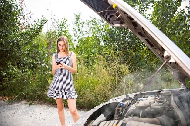 그 젊은 여성은 휴식을 취하다가 차를 부수 었습니다. 그녀는 스스로 고장난 것을 고치려고하거나 히치 하이킹을해야합니다. 긴장된다. 주말, 도로 문제, 휴가.