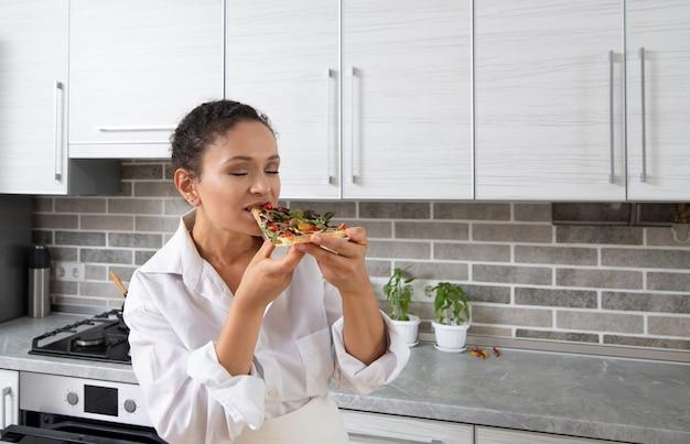 若い女性シェフはチーズなしのビーガンピザを味わい、喜んで目を閉じました。