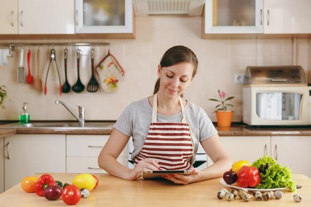 Молодая женщина режет овощи на кухне ножом и ноутбуком на столе. овощной салат. концепция диеты. здоровый образ жизни. готовим дома. готовить пищу.