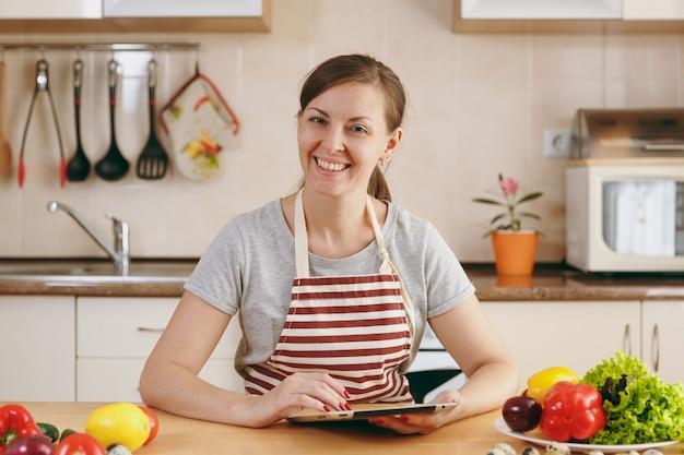 젊은 여성은 식탁에 칼과 노트북을 들고 부엌에서 야채를 자른다. 야채 샐러드. 다이어트 개념입니다. 건강한 생활. 집에서 요리하기. 음식을 준비하다.