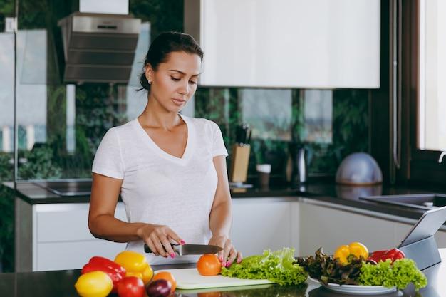 若い女性はテーブルの上のナイフとラップトップでキッチンで野菜を切る