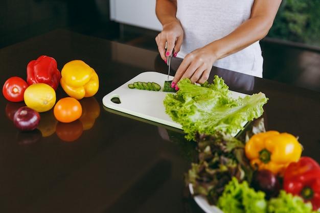 젊은 여자가 칼로 부엌에서 야채를 자른다.