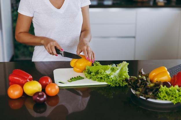 若い女性はナイフで台所で野菜を切る