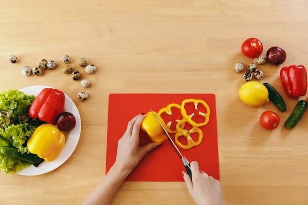 若い女性は台所でナイフでサラダのために黄ピーマンを切ります。ダイエットの概念。健康的な生活様式。家で料理。食べ物を用意します。上からの眺め。