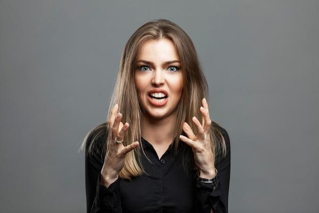 Молодая женщина злится и кричит. красивая блондинка в черной рубашке. негатив и агрессия. серый фон.