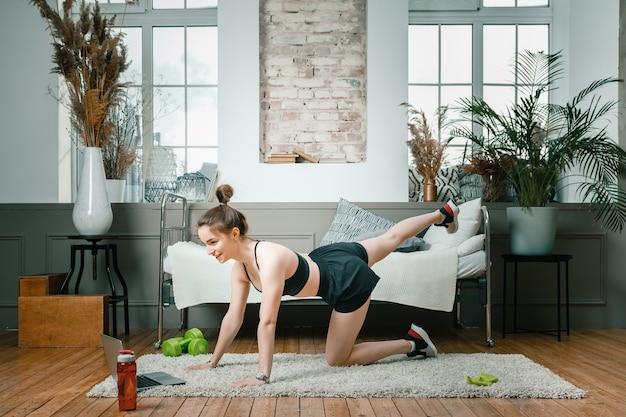 若い女性は家でスポーツに行きます。黒髪の陽気なスポーツウーマンは、脚を作り、映画を見て、寝室のラップトップから勉強します