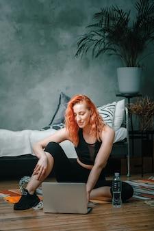 若い女性は家でスポーツに行きます。自宅の床で休んでいる赤い髪の陽気なスポーツウーマン、映画を見たり、寝室のラップトップから勉強したりする