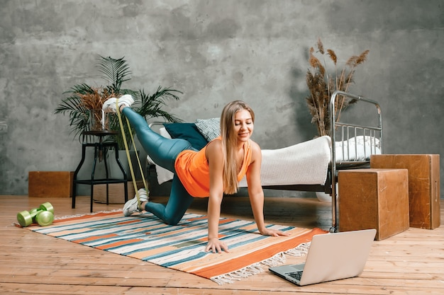 Молодая женщина занимается спортом дома