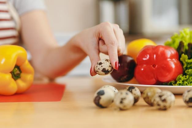 若い女性は台所でウズラの卵を手に持っています。ダイエットの概念。健康的な生活様式。家で料理。食べ物を用意します。閉じる。