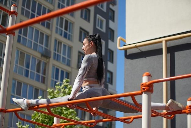 운동복을 입은 젊은 여성이 금속 구조물 위에 꼬기 위에 앉아 앞을 똑바로 바라 봅니다.