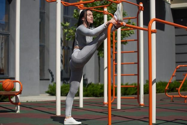 운동복을 입은 젊은 여성은 운동을하고 훈련 전에 다리 근육을 펴고 고르지 않은 막대에 다리를 던졌습니다.
