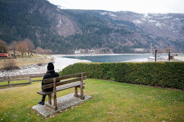 Молодая женщина в теплой одежде сидит одна на деревянной скамейке и смотрит на озеро в холодный день.
