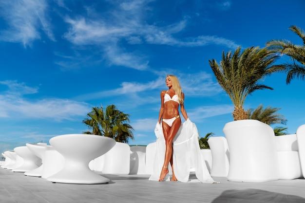 Молодая женщина в белом парео на террасе и голубом небе