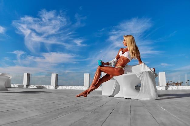 テラスと青い空に白いパレオの若い女性