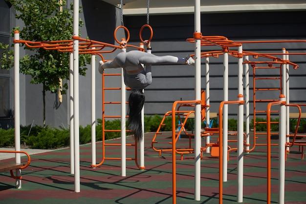 Девушка занимается гимнастическими кольцами. она висит вверх ногами, ноги на шпагате.