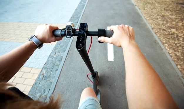 젊은 여성은 통로를 따라 저녁 도시를 통해 전기 스쿠터를 타고 있습니다.