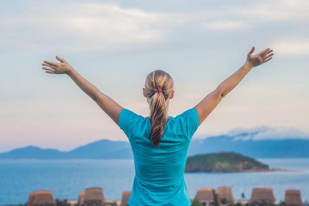 若い女性は、雲のある海、岩、空に向かって、太陽に向かって手を上げました。