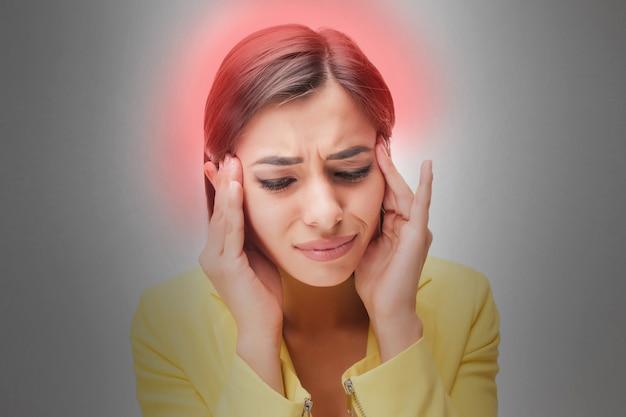 Портрет молодой женщины с болевыми эмоциями на сером фоне. концептуальная головная боль