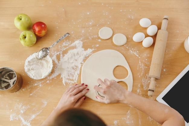 小麦粉を持ってテーブルに座っている若い女性は、キッチンで餃子のために生地の円でガラスを切り取りました。クッキングホーム。食べ物を用意します。上面図。