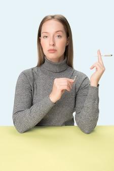 スタジオのテーブルに座ってタバコを吸う若い女性。トレンディな色。コピースペースとミニマリズムスタイルの白人の女の子の肖像画