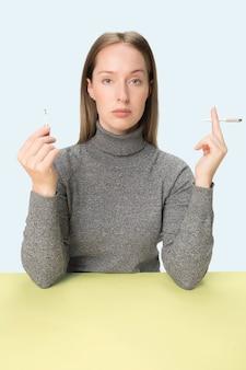 スタジオのテーブルに座ってタバコを吸う若い女性。トレンディな色。コピースペースとミニマリズムスタイルの白人の女の子の肖像画 無料写真