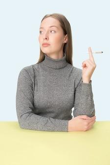スタジオのテーブルに座ってタバコを吸う若い女性。