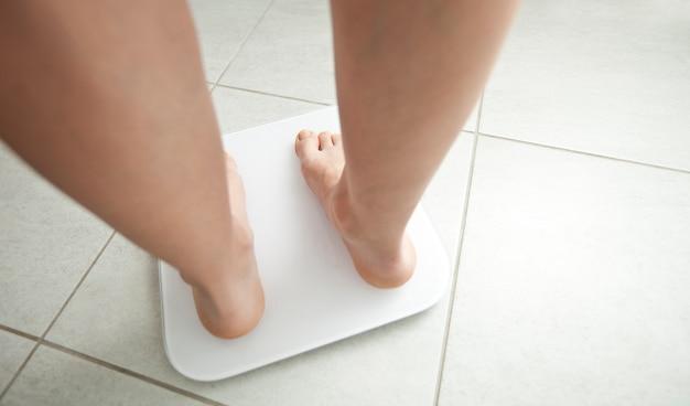 若い女性はバスルームの体重計の上に立つ
