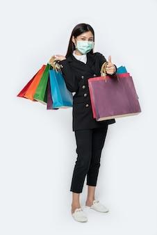 若い女性はマスクを身に着けて暗闇の中で服を着て、買い物にバッグを持っていました