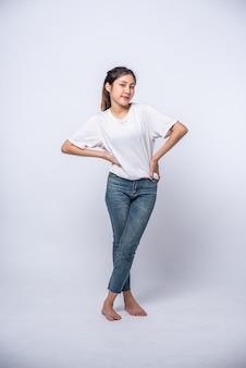 若い女性は白いシャツを着ていて、腰に手を当てていました。