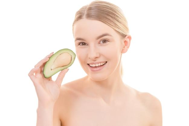 Молодая женщина с авокадо на белом фоне