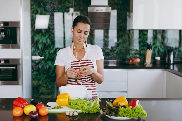 テーブルの上にラップトップとキッチンで野菜を手に持って耳にヘッドフォンを持つ若い女性