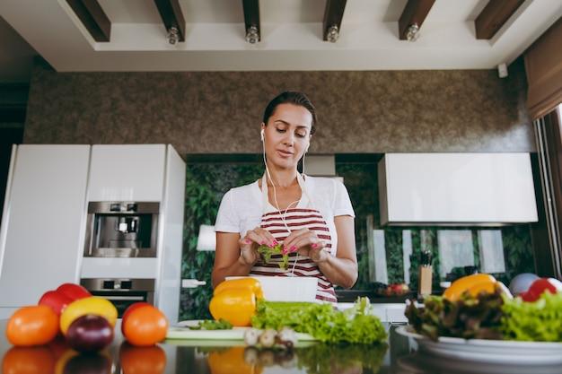 테이블에 노트북과 부엌에서 손에 야채를 들고 귀에 헤드폰을 가진 젊은 여자