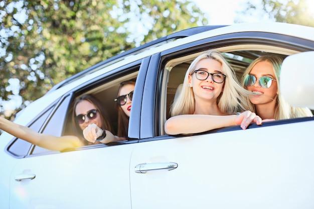車に座って屋外で笑顔の若い女性。ライフスタイル、旅行、冒険、女性の友情のコンセプト