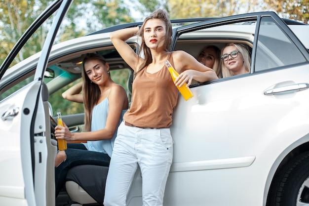 차에서 젊은 여성이 웃고 주스를 마시는