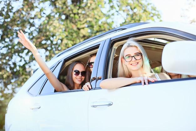 웃고있는 차에있는 젊은 여성들