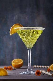 Тей ликер с лимоном в бокале для мартини на сером столе