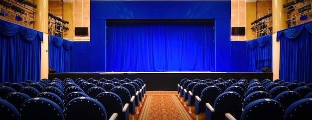 파란색 빈 좌석과 닫힌 커튼이 있는 극장 내부 전망