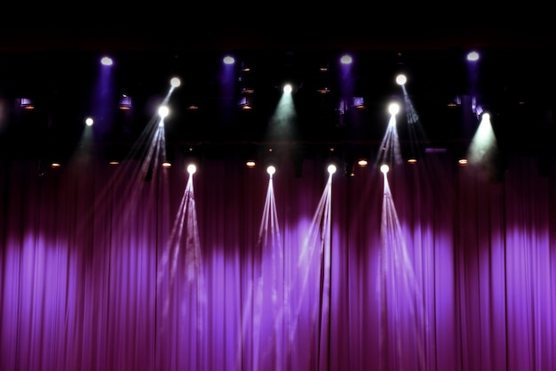 Theater stage with purple curtains and spotlights.