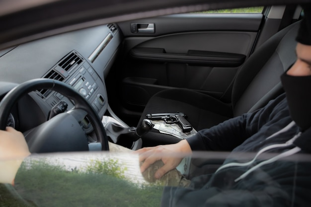 Theft of the car. man behind the wheel. gun with money lying on the seat. carjacking of vehicle. robbing and crime.
