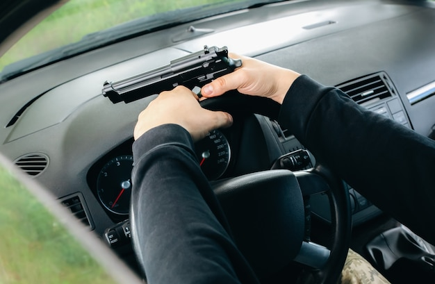Theft of the car. man with gun behind the wheel. carjacking of vehicle. robbing and crime.