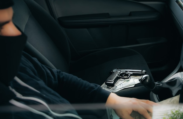 Кража автомобиля. человек за рулем. пистолет с деньгами, лежащими на сиденье. угон автомобиля. грабежи и преступление.