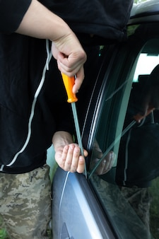 Кража автомобиля. мужчина открывает дверь. угон автомобиля. грабежи и преступление.