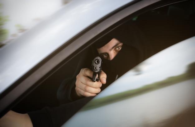 Кража автомобиля. человек с ружьем за колесом. угон автомобиля. грабежи и преступление.