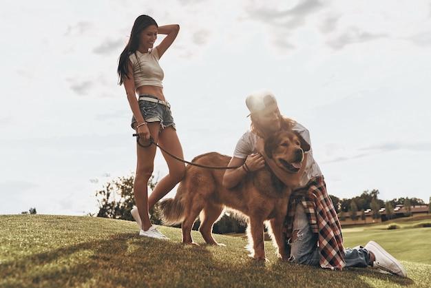 彼らの親友。公園で彼のガールフレンドと自由な時間を過ごしている間彼の犬を抱きしめるハンサムな若い男