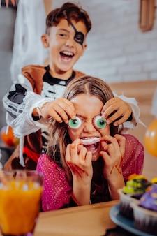 テーマスイーツ。ハロウィーンのテーマのお菓子を食べている間、兄弟と子供たちは非常に面白いと感じています Premium写真
