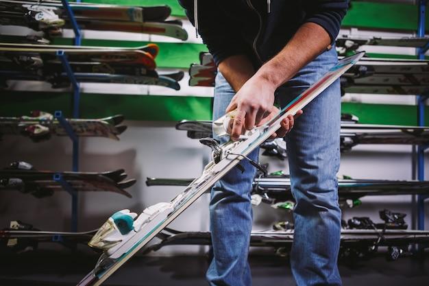 Тема бизнеса по продаже и сервису горнолыжного снаряжения. в руках молодого кавказца горные лыжи, проверяет и регулирует застежку на ботинке. на стене стенд с лыжами в магазине.