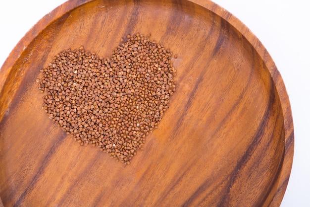 Тема диеты и потеря веса на белом фоне. гречка в деревянной тарелке выложена в форме сердца.