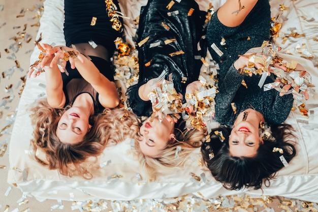 테마 파티. 침착 해. 색종이 비가 아래 침대에서 편안한 블랙 여성 그룹. bff 여성 모이는 흥분.