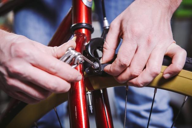 テーマリペアバイク。白人男性の手のクローズアップは、赤い自転車にリムブレーキを調整して取り付けるために、ハンドツールの六角形セットを使用しています。